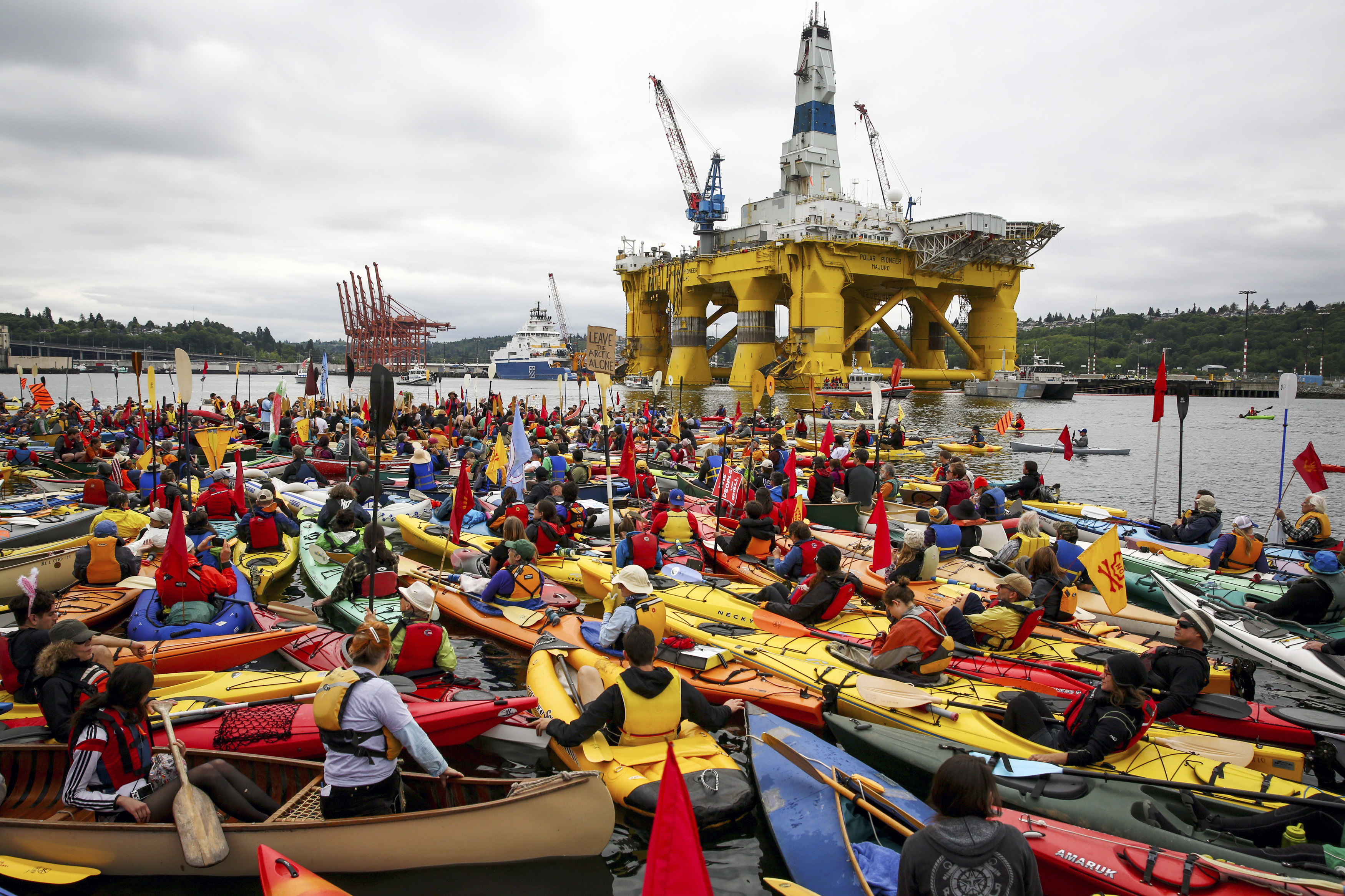 """Activists who oppose Royal Dutch Shell's plans to drill for oil in the Arctic Ocean prepare their kayaks for the """"Paddle in Seattle"""" protest on Saturday, May 16, 2015, in Seattle. The protesters gathered at a West Seattle park and then joined hundreds of others in Elliott Bay, next to the Port of Seattle Terminal 5, where Shell's Polar Pioneer drilling rig is docked. (Daniella Beccaria/seattlepi.com via AP) MAGS OUT; NO SALES; SEATTLE TIMES OUT; TV OUT; MANDATORY CREDIT"""